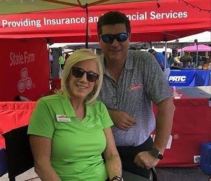 mand and woman working the SERVPRO tent at the 19th Annual Squealin on the Square