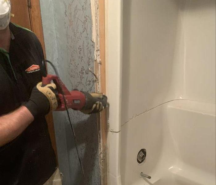 SERVPRO technician removing a shower from a home after severe water damage
