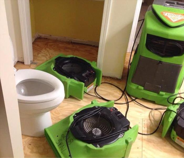 Air dryers drying out a residential bathroom after a water supply line burst.
