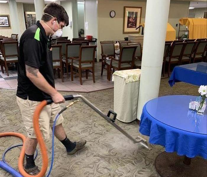 SERVPRO Technician cleaning the carpet in the dining hall of a Retirement Home.