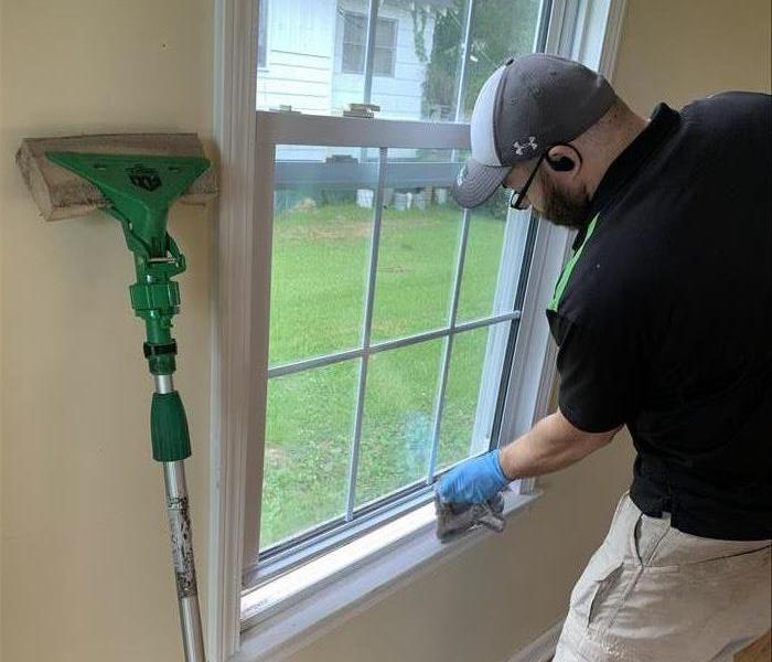 Our SERVPRO technician cleaning the window seals of Soot Damage from a house fire in Clinton, SC