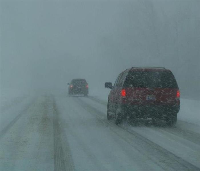Motorist traveling the snow-covered highway during a winter storm.