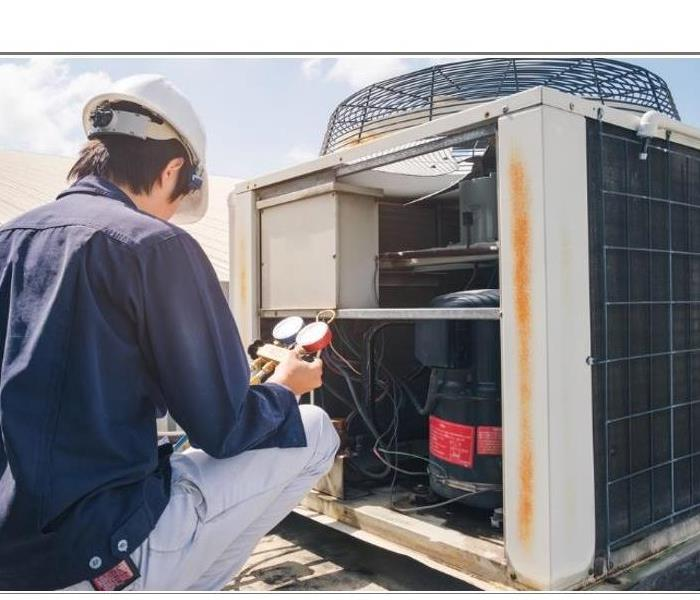 Technician Servicing a Commercial HVAC unit for issues